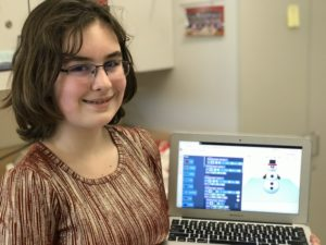 Alexandra Wyatt holds a laptop showing her snowman design.